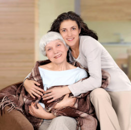 elderly woman and her daughter sitting in a chair with a blanket
